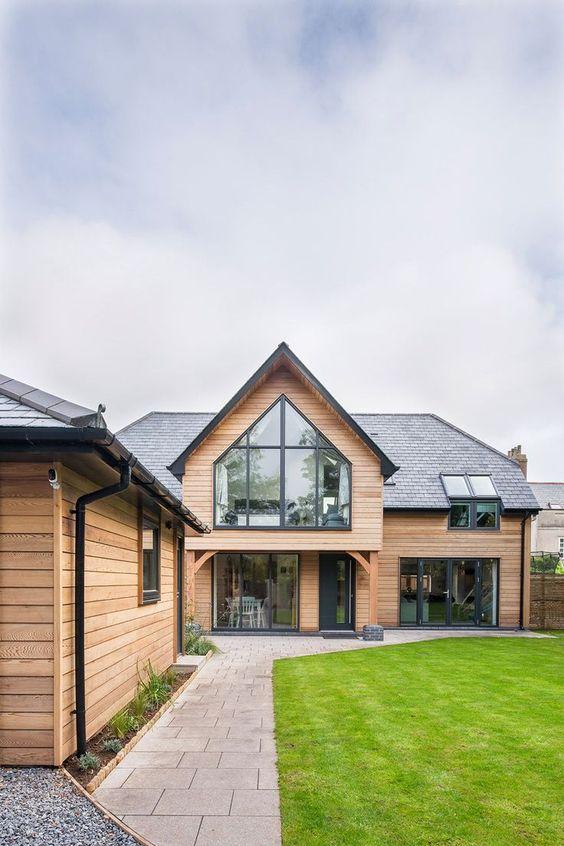 Casa con fachada de madera con grandes ventanales