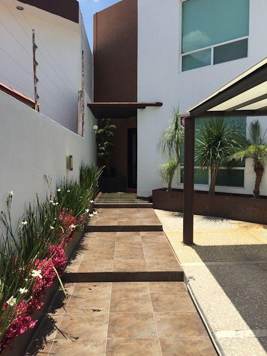 Fachada de casa con jardineras en el piso