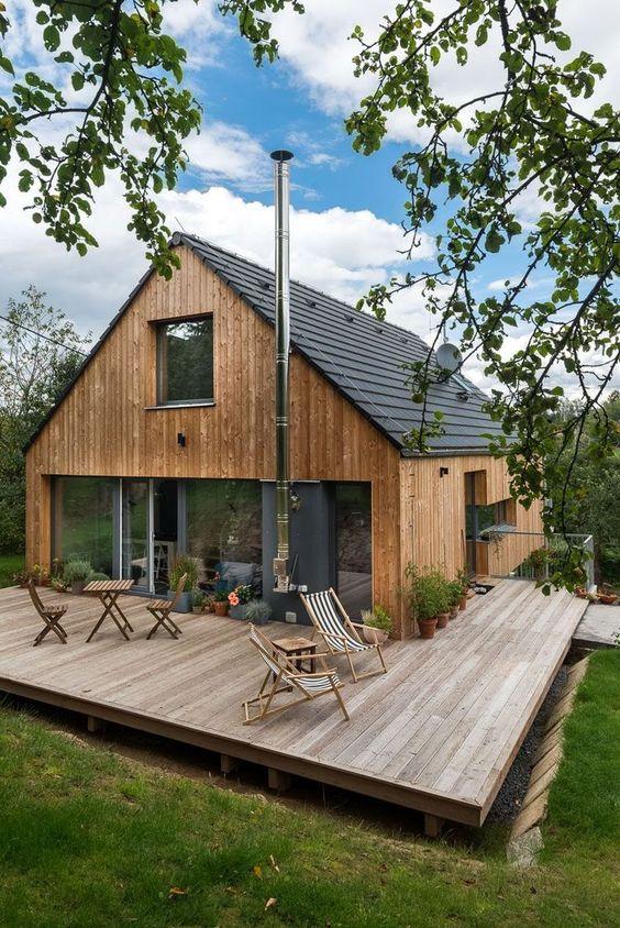 Fachada de casa con material y terraza de madera