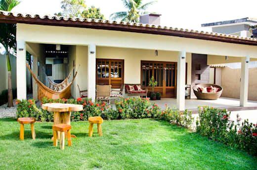 Fachada de casa rústica con jardín frontal