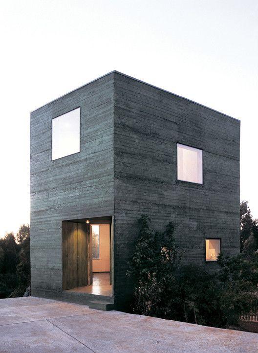 Casa cuadrada de dos pisos con fachada oscura